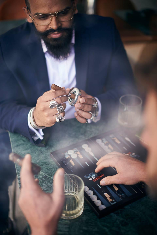 Lifestyle photography of man holding cigar playing backgammon