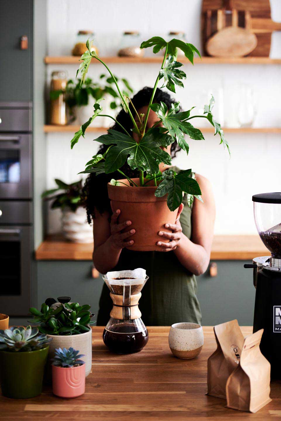 Lifestyle photography of woman holding plant - coffee in home by London photographer Del Manning